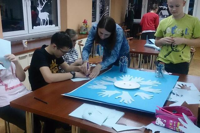 przy stole na którym leży duży niebieski karton naklejane są białe obrysy dłoni. przy stole siedża chłopiec i dziewczynka nad nimi nachyla się nauczycielka