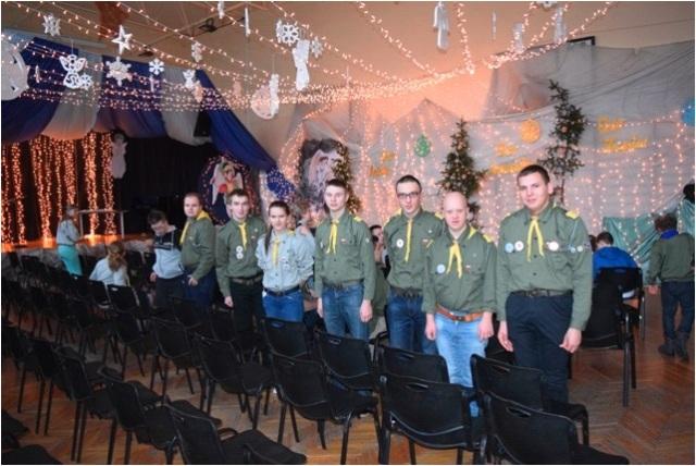 harcerski opłatek, siedmiu harcerzy stoi w szeregu przy czarnych krzesłach z tyłu siedzą inne osoby, sala udekorowana girlandami i świątecznymi ozdobami,