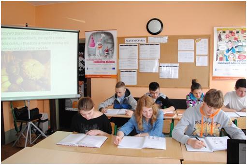 7 uczniów w dwóch rzędach siedzi przy ławkach, patrzą na dól na zeszyty. Po lewej stronie ekran rzutnika na nim wyświetlony proces pieczenia chleba.