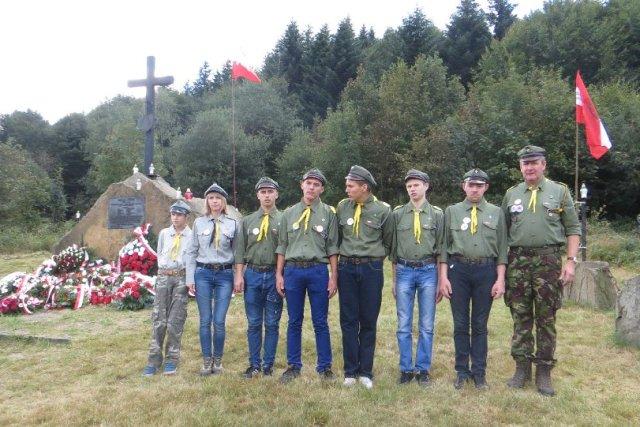 Sucha Polana, ośmiu harcerzy stoi w szeregu, za nimi pomnik z krzyżem i wieńcami, z tyłu las