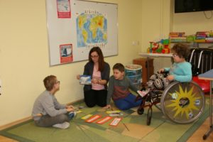 W sali lekcyjnej nauczycielka z dwoma chłopcami siedzi na dywanie . Nauczycielka trzyma w ręce kartkę z zadaniami. na podłodze leża wyrazy na kolorowych kartonikach. z tyłu biała tablica na której przyczepiona jest mama świata.