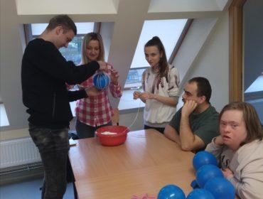 W pomieszczeniu przy stole, grupka osób. Na stole leży czerwona miska, 5 niebieskich balonów, spinacze, nożyczki oraz ścierka kuchenna. Uczniowie uczestniczą w pokazie robienia bombek z włóczki. Jeden z nich trzyma niebieski balon i owija go włóczką, pomaga mu w tym ubrana w biało- czerwoną koszulę kobieta. Obok stoi uczennica, trzyma w ręku włóczkę. Przy stole siedzi chłopak przygląda się, siedząca obok niego dziewczyna patrzy przed siebie. W tle okna dachowe.