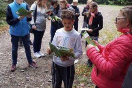 Pięciu uczniów w wieku nastoletnim stoją w grupie, w półokręgu zwróceni twarzami do siebie. Za nimi widać las. W rękach trzymają książki, czytają z zaciekawieniem.
