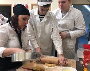 W pomieszczeniu, przy szarym blacie kuchennym stoją ubrane na biało 3 osoby. Z przodu po lewej stronie kobieta w czarnym czepku trzyma metalową, okrągłą formę do pieczenia. Obok niej dwóch uczniów. Jeden z nich w białym czepku z daszkiem na stolnicy wałkuje ciasto. Na stolnicy leży druga porcja ciasta, duży nóż z czerwoną rączką oraz biała miseczka z żółtym płynem. Tuż obok żółta ścierka kuchenna. Obok osoby wałkującej ciasto, przygląda się postawny chłopak. Z tyłu na ścianie zegar.