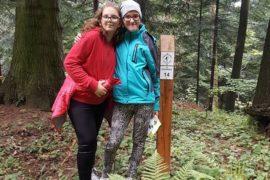 2 Dziewczyny stoja przy słupie z informacją o gatunkach drzew. Otoczenie lasu.
