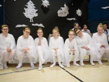 Na pierwszym planie zdjęcia widać siedem dziewczynek siedzących na ławeczce. Wszystkie się uśmiechają, są ubrane na biało i mają na sobie białe pelerynki. Na włosach mają złote opaski z gwiazdkami. Dziewczynki siedzą na tle dekoracji : wyciętej z białego papieru choinki, kościółka, chmur i gwiazdy. Z boku z tyłu za dziewczynkami siedzi grupa osób.