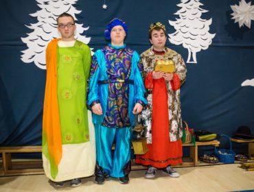 Na zdjęciu widać trzech chłopców w strojach króli. Chłopiec stojący z lewej strony ma na sobie żółtą szatę a na niej tunikę w kolorze zielonym. Na ramieniu pomarańczowy szal. W środku stoi chłopiec w niebieskim kostiumie w lewej ręce trzyma kadzidło. Obok niego stoi chłopiec w czerwonej szacie, złotym płaszczu na ramionach , na głowie ma koronę a w rękach trzyma złote pudełko.