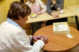 Z przodu pochylona postać pielęgniarki czyta kartkę. Z tyłu dwoje nastolatków siedzi za ławką. Po prawej chłopiec podpiera brodę. Po lewej dziewczyna siedzi wyprostowana.