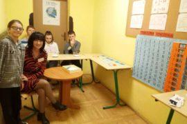 Korytarz szkolny. Na pierwszym planie ciemnowłosa kobieta, w czerwono-czarnej sukience. Siedzi przy okrągłym, drewnianym stoliku, patrzy przed siebie i uśmiecha się. Tuż za nią w szkolnej ławce siedzą trzy osoby, dwóch chłopców i jedna dziewczyna. Po lewej stronie ławka, na której leżą kolorowe kartoniki. Z tyłu na drzwiach plakat.