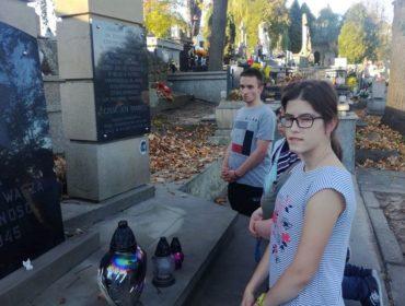 Dziewczyna i chłopak modlą się przed grobem, pomnikiem nieznanego żołnierza. Na pomniku stoją znicze .