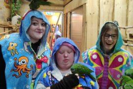 Na zdjęciu znajdują się 3 osoby. Wychowawca i 2 dziewczynki. Wszyscy ubrani są w ochronne ręczniki. Na głowie wychowawcy siedzi papuga. U 1 z dziewczynek papuga siedzi pod ramieniem, a ona karmi papugę. U drugiej dziewczynki 2 papugi siedzą na ręce i jedzą pokarm z kubka