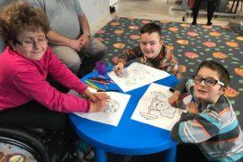 Przy okrągłym, niebieskim stoliku siedzi dwójka chłopców na dywanie. Na wózku inwalidzkim siedzi uśmiechnięta dziewczynka. Dzieci kolorują ilustracje.