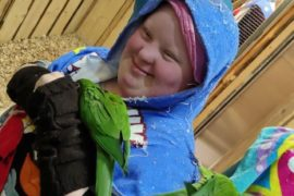 Na pierwszym planie dziewczyna trzyma zieloną papugę. Za nia kobieta opiekunka zwierząt. obie znajdują się w pomieszczeniu dla papug.