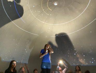 Kobieta, astronom, w niebieskiej koszulce stoi, obok niej siedzi grupa dzieci patrzą w górę. Wszyscy są w wielkim balonie na ścianach którego wyświetlane są gwiazdy.