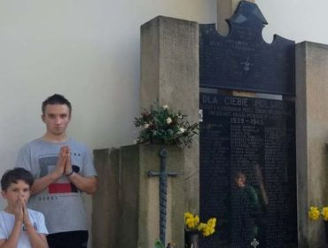 Dwóch chłopców stoi ze złożonymi rękami. Po prawej ogromny pomnik cmentarny.