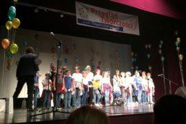 Na scenie stoi grupa siedmiu dziewcząt. Są ubrane w kolorowe stroje. Na głowach mają czapki z daszkiem. W rękach trzymają czerwone pompony. Przed nimi stoją mikrofony na stojaku. W tle sceny widać kolorowe balony.