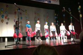 Grupa dzieci w kolorowych strojach stoi na scenie. Mają na głowach czapki z daszkiem. Obok nich widać kolorowe balony. Dzieci są radosne i uśmiechnięte. Wśród nich jest chłopiec na wózku inwalidzkim. Przed dziećmi stoją mikrofony na stojaku.