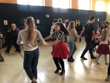 Dwie dziewczynki tańczą. Jedna z nich ubrana jest w czerwoną spódnice i bluzkę w biało-czarną kratę. Druga w dżinsy i bluzkę w biało-czarne paski. Za dziewczynkami widać tańczące dzieci w kole.