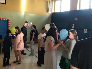 Taniec z balonami. Na zdjęciu tańczą cztery pary. Wszyscy uśmiechnięci. Każda para trzyma balona głowami, żeby nie upadł.