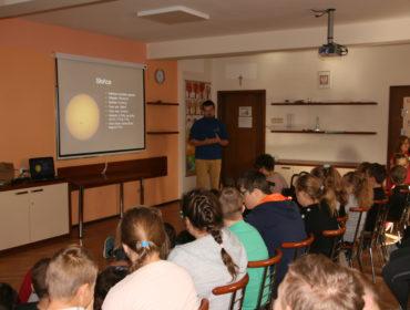 W dużej sali jest ciemno. Na pierwszym planie grupa uczniów siedzi na krzesłach i patrzą na ekran na którym wyświetlane jest słońce z opisem gwiazdy. Po prawej stoi pan astronom, wyjaśnia zawiłości o kosmosie.