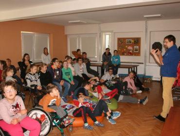 Grupa dzieci w dużej sali siedzi na krzesłach, na pufach. Z lewej chłopiec i dziewczynka na wózkach inwalidzkich. Po prawej pan astronom w niebieskiej koszulce liczy na palcach.