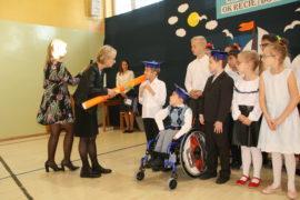 Na zdjęciu widać grupę dzieci. Jeden chłopiec siedzi na wózku inwalidzkim. Przed nim stoi Pani dyrektor Irena Jamróz. Pani dyrektor kładzie chłopcu na wózku na ramieniu duży ołówek z papieru.