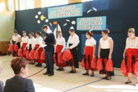 Grupa dziewcząt w białych bluzkach i czerwonych oraz czarnych spodniach stoi w rzędzie. W rękach mają czerwone pompony do tańca. Przed nimi stoi chłopiec z mikrofonem i kartka. Czyta tekst do mikrofonu. W sali jest jasno.