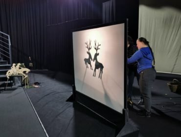 Na pierwszym planie biały podświetlony ekran na którym widać dwa renifery. Z tyłu za ekranem widać postać dziewczyny w niebieskiej bluzie ktora trzyma rekwizyt wyświetlany na ekranie.