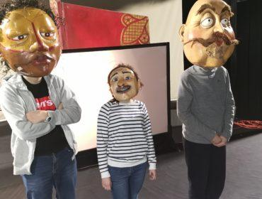 Trzy osoby w ogromnych maskach w kształcie głów. Po lewej wysoka postać w masce o ciemnej karnacji i lekko kręconych włosach, na środku mała postać w bluzie w paski w masce o jasnej karnacji, małe wąsy. Po prawej wysoka postać w dużej masce w kształcie głowy o jasnej karnacji i ogromnych oczach i wąsach.