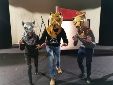 3 osoby w maskach zwierząt na głowie. Po prawej żółta maska lwa, na środku żółto czarna maska tygrysa, po lewej szara maska wilka. Osoby stoją w wykroku udają ruchy zwierząt.