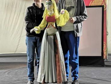 Na środku stoi dwóch chłopców po prawej niższy po lewej wyższy. Chlopcy r rękach trzymają duża kukiełkę, postać kobiety w pięknym arabskim stroju.