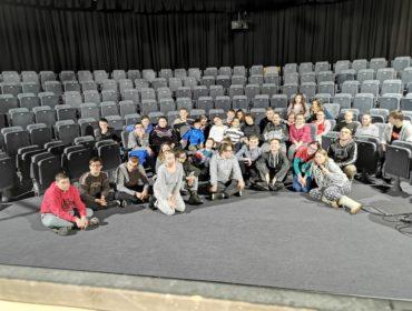 Na pierwszym palnie grypa kilkunastu uczniów siedzi na podłodze, za nimi kilkunasty uczniów siedzi na krzesłach teatralnych. Wszyscy znajdują się w sali teatralnej. Podłoga i krzesła są szare.
