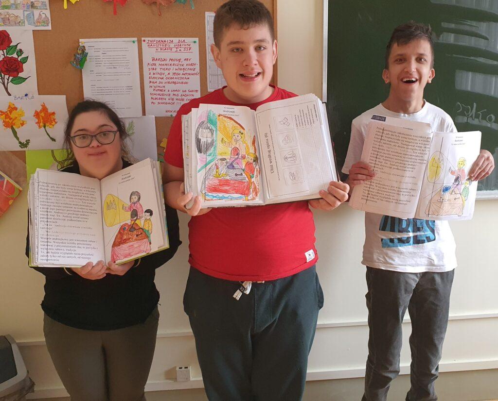 Przed tablicą korkową i zieloną stoi dziewczynka i dwóch chłopców. Wszyscy są uśmiechnięci. Trzymają otwarte zeszyty i prezentują swoje prace związane z andrzejkami.