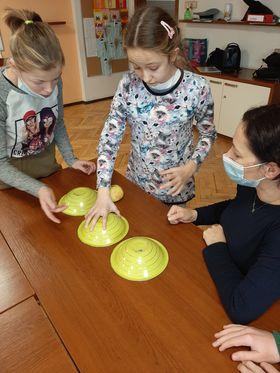 Dwie dziewczynki stoją przy stole, na którym leżą trzy żółte miski. Dziewczynki pokazują pani, którą miskę ma obrócić, by zobaczyć wróżbę.
