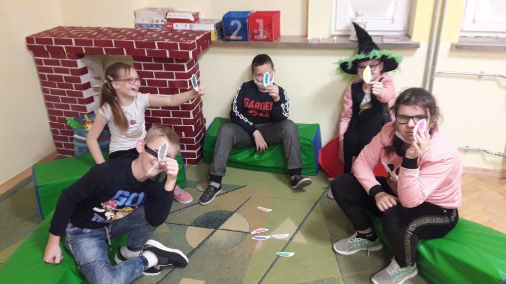 Pięcioro dzieci siedzi w kręgu w ręce trzymają pióra z papieru. Jedna z dziewczynek ma czapkę czarownicy.