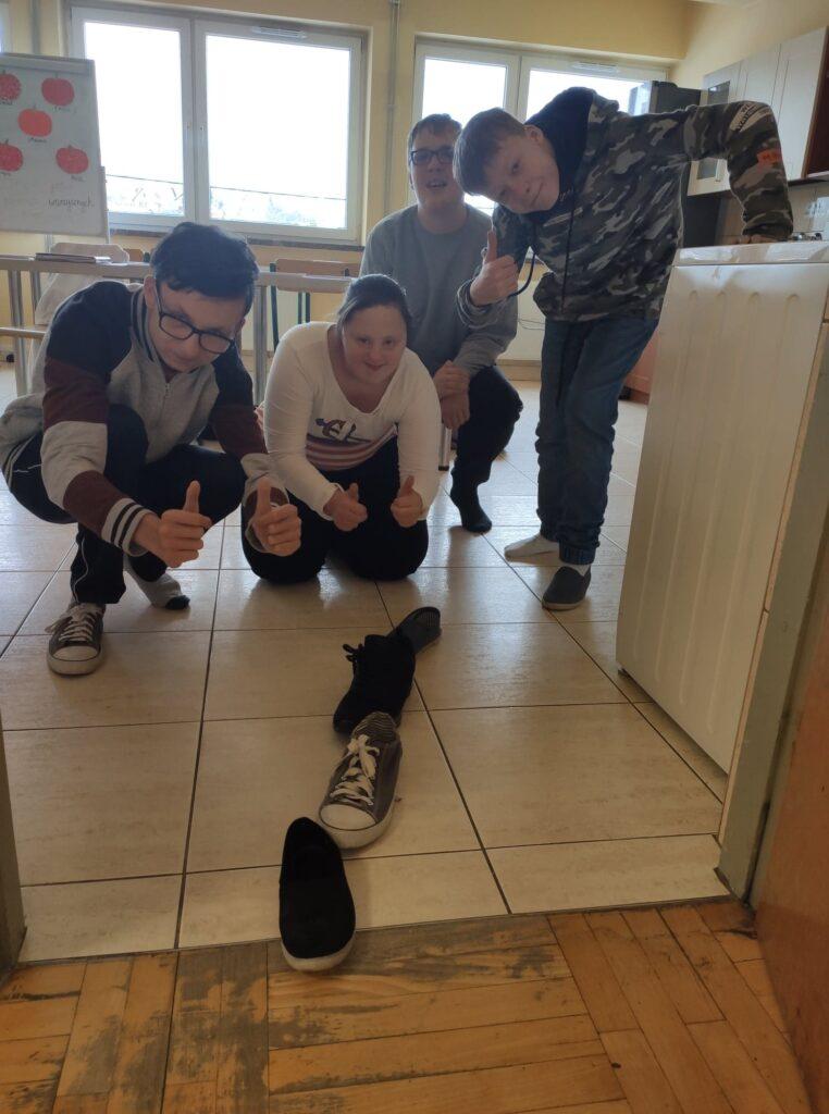Trzech chłopców i jedna dzieczynka stoją w progu klasy, przed nimi buty ułożone jeden za drugim,