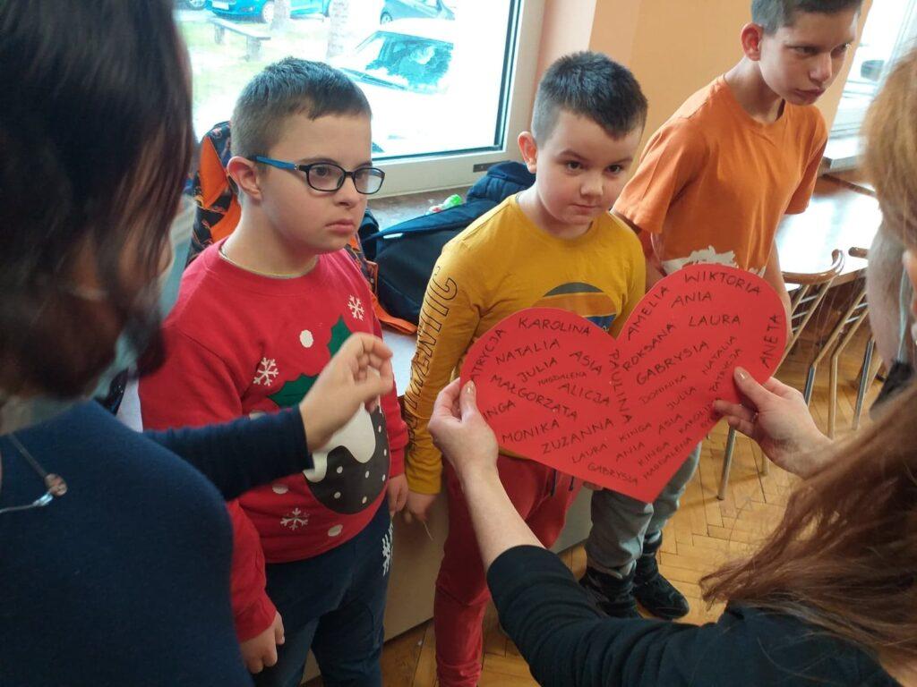 Pani trzyma duże czerwone serce z wypisanymi imionami dziewcząt. Chłopcy przebijają igłą serce.