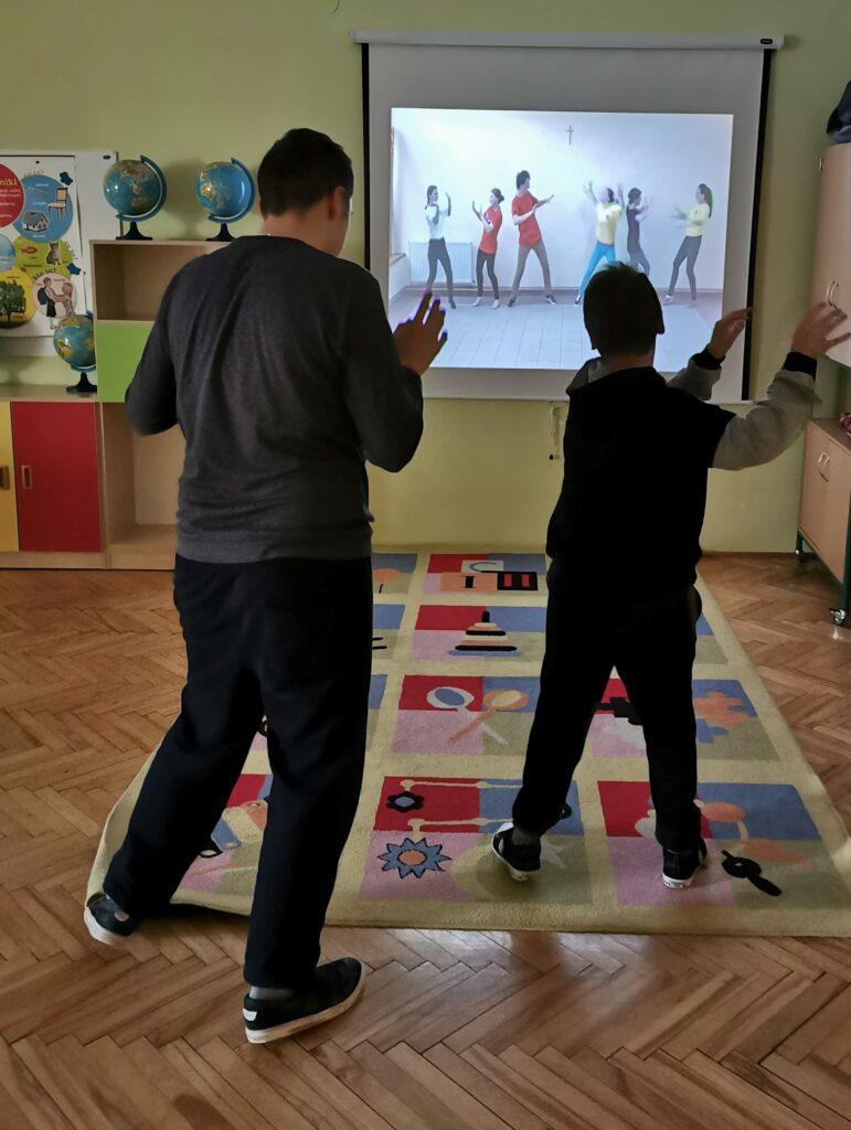 Dwóch chłopców stoi przed rzutnikiem z wyświetloną prezentacją taneczną. Chłopcy wykonują ruchy jakie zaprezentowane są na prezentacji.