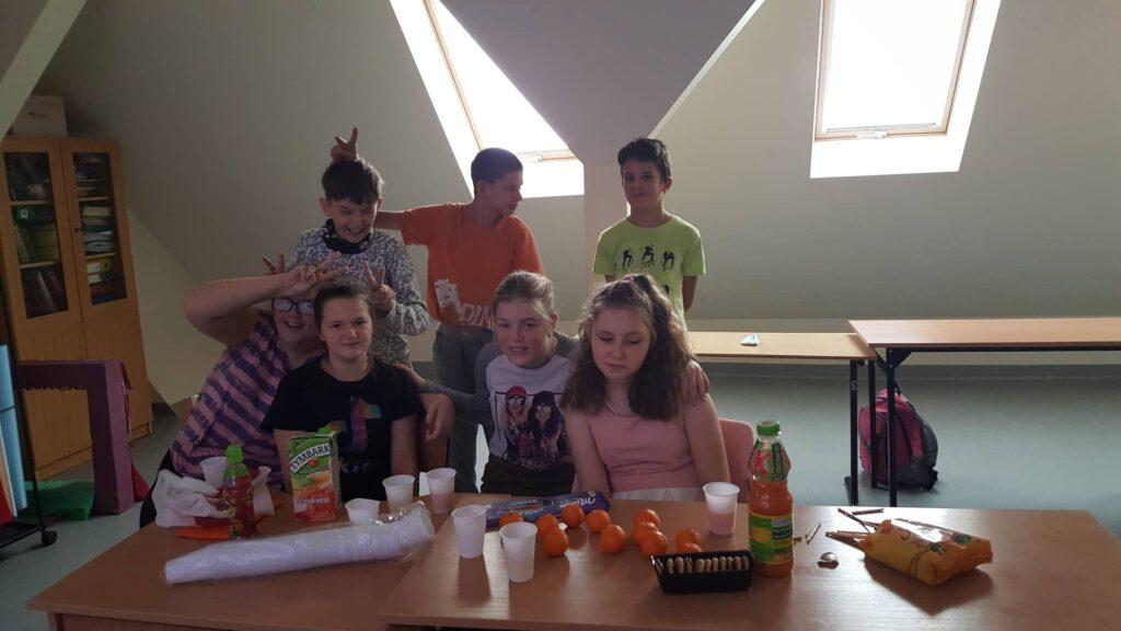 Cztery dziewczynki siedzą przy stole, na którym leżą mandarynki, napoje i słodycze. Za dziewczynkami stoi trzech chłopców. Wszyscy są uśmiechnięci.