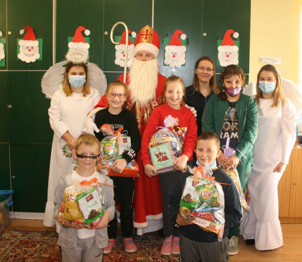 sześć dziewczynek i dwoje chłopców stoi z prezentami, za nimi stoi Mikołaj z biała brodą