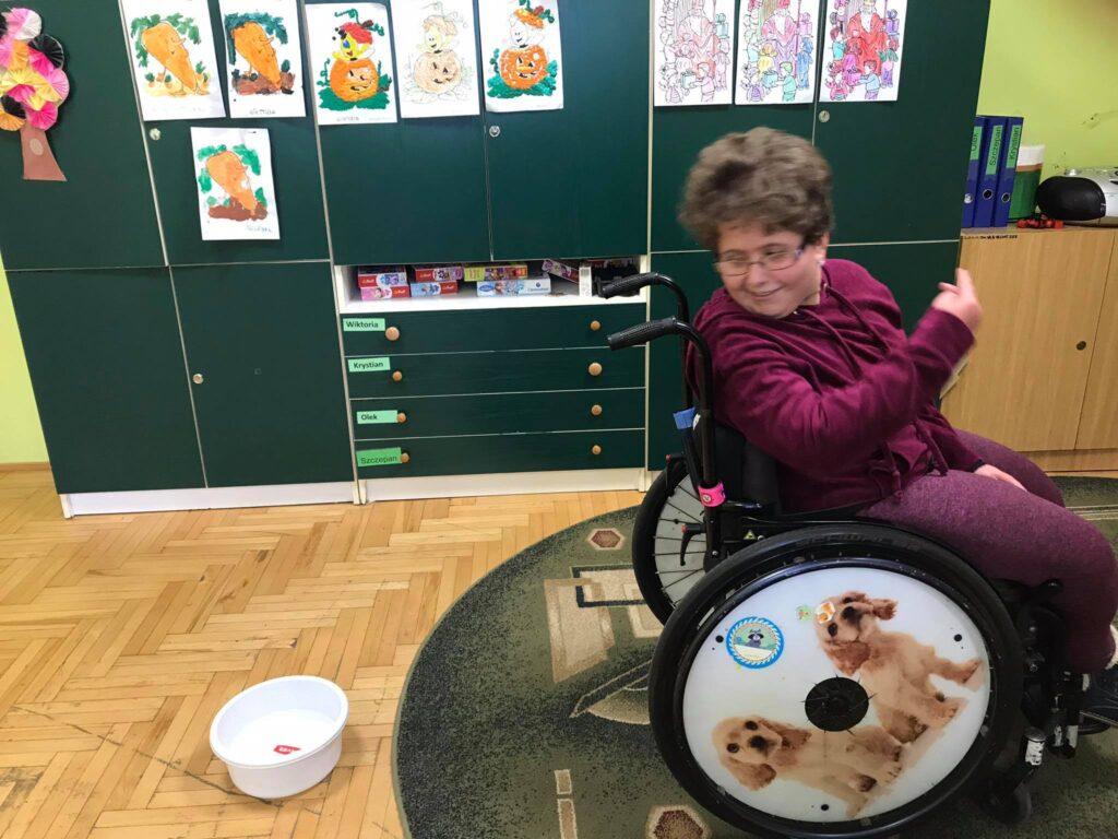 Dziewczynka siedzi na wózku inwalidzkim. Metr za wózkiem jest miska z wodą. Dziewczynka rzuca monetę do tyłu.