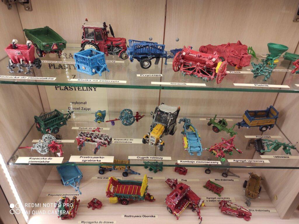 plastelinowe maszyny rolnicze , ułożone na trzech szklanych półkach