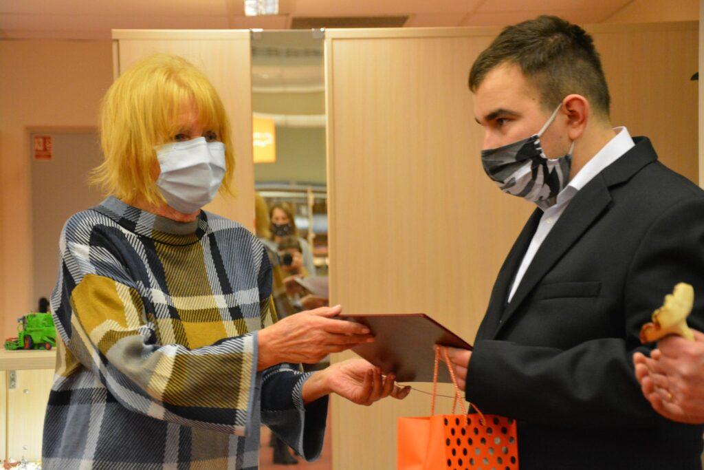 z lewej pani wręcza dyplom i nagrodę chłopcu, chłopiec z lewej oboje mają na twarzy maski
