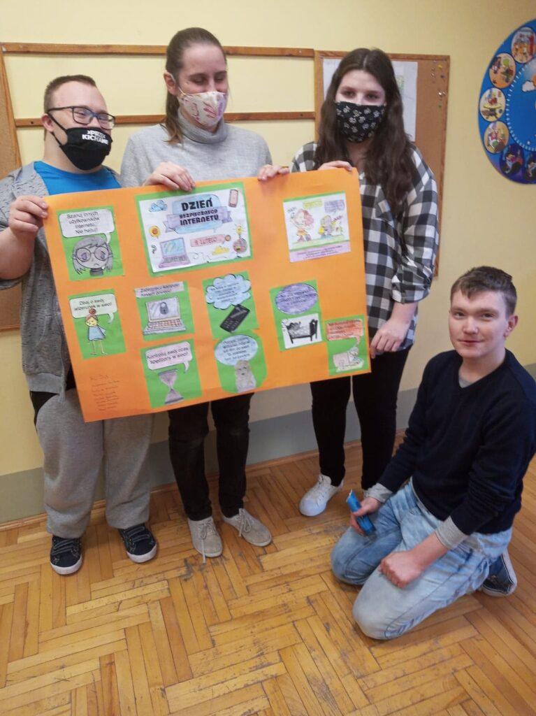 troje uczniów trzyma pomarańczową duża kartkę, jeden chłopieć kuca przed nimi