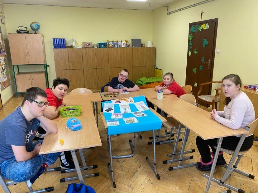 pięcioro dzieci siedzi za ławkami przed nimi niebieski plakat