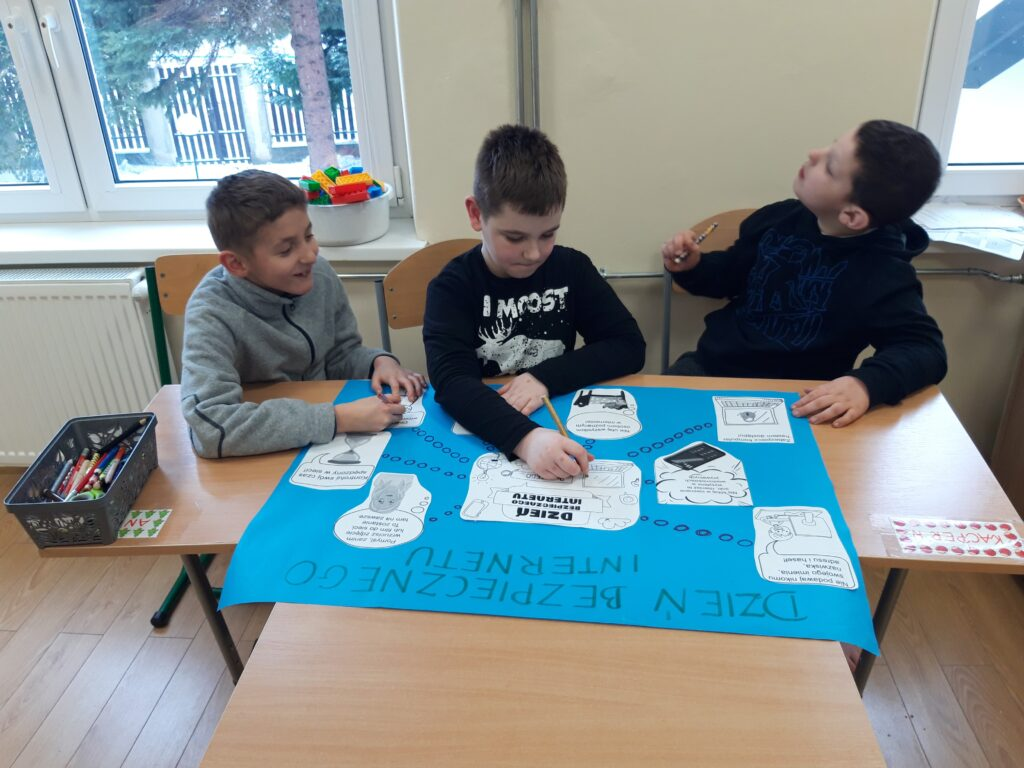 trzech chłopców siedzi na krzesłach przed nimi niebieska duża kartka