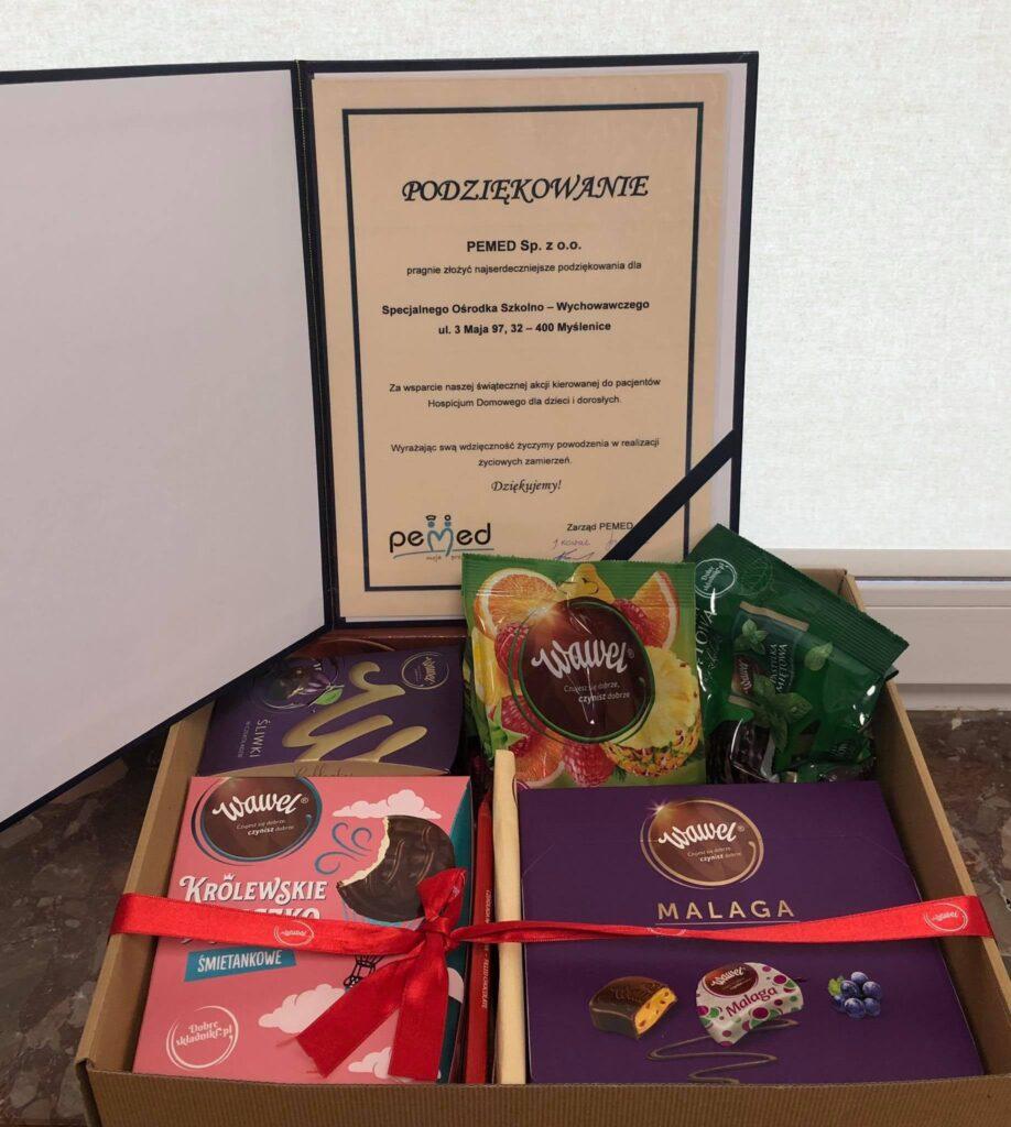 na pierwszym planie słodycze przewiązane wstążką, z nimi dyplom z podziękowaniami