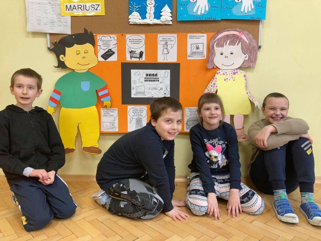 trzech chłopców i jedna dziewczynka siedzą przed plakatem na żółtym dużym kartonie