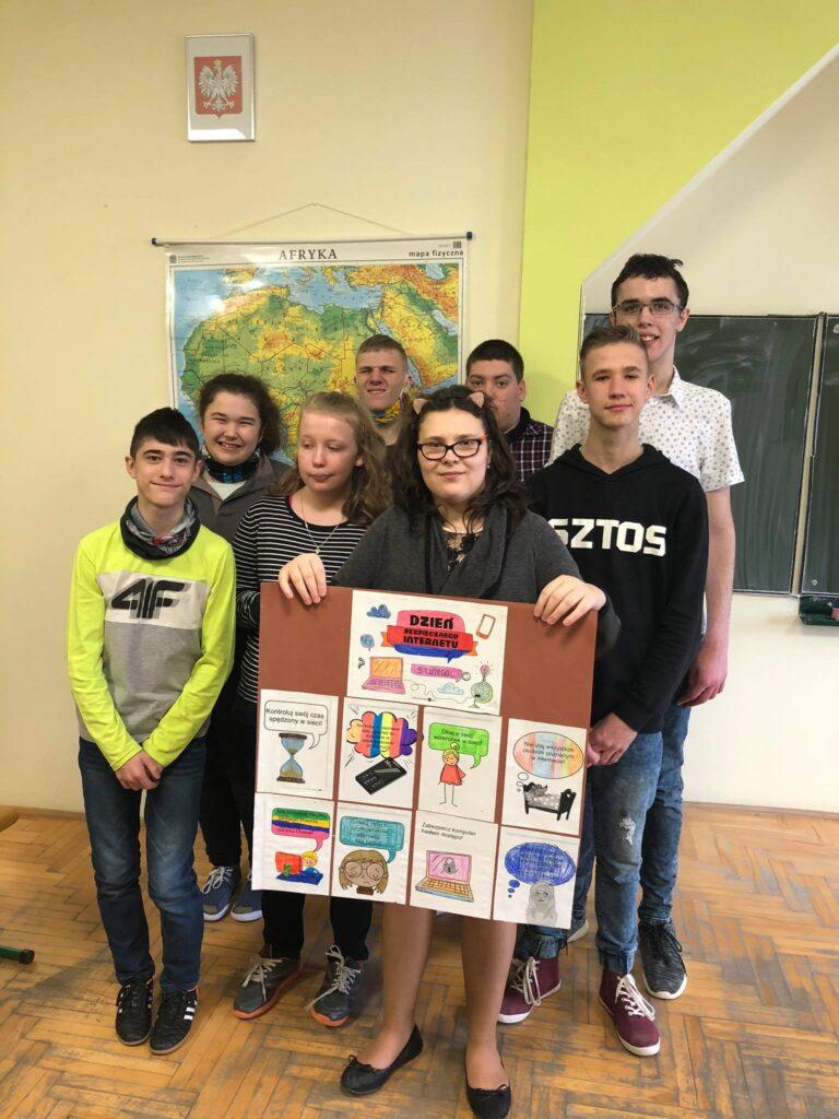 grupa uczniów stoi i trzyma plakat