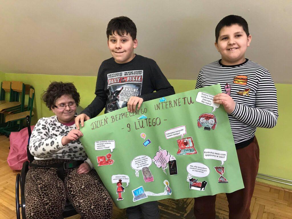 jedna dziewczynka na wózku inwalidzkim i dwóch chłopców trzymają zieloną kartkę z plakatem